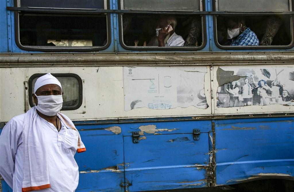 印度4日通報新增近萬例確診,國防部次長庫瑪也染疫,是印度目前中鏢的最高階官員。圖為印度東部民眾乘坐巴士配戴口罩防疫。(美聯社)