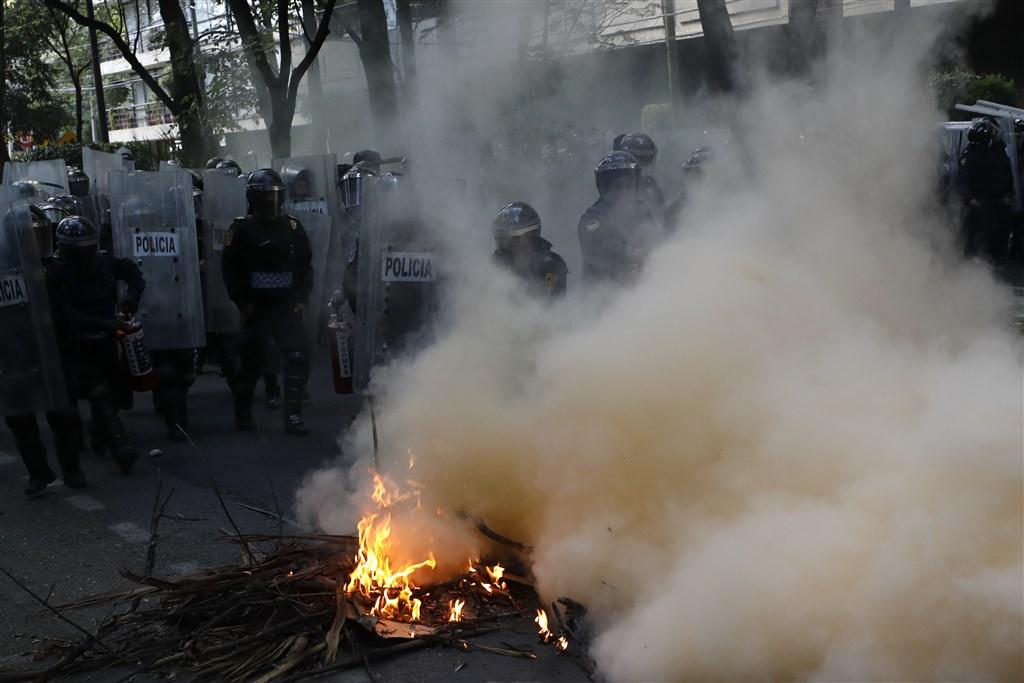 墨西哥群眾5日抗議警察濫用武力,沿途破壞建築物並朝美國大使館丟擲汽油彈。(美聯社)