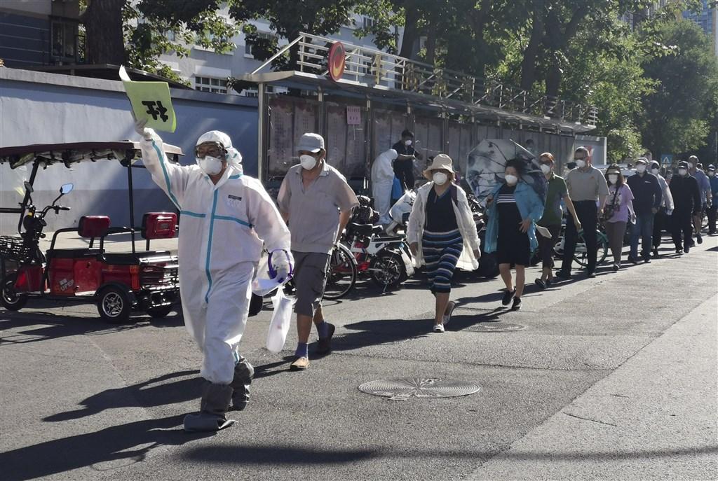 北京市14日下午宣布,全市凌晨0時至早上7時又新增8例武漢肺炎確診病例。圖為14日北京市民列隊至一處體育館接受採檢。(中新社提供)