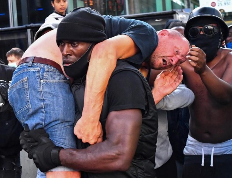 英國倫敦市中心13日的和平反種族歧視示威活動變調,演變成暴力衝突,路透社記者拍下非裔壯漢扛受傷白人走出混亂場面的照片,與反種族歧視和極右派抗議群眾互相毆打的場景形成對比。(路透社提供)