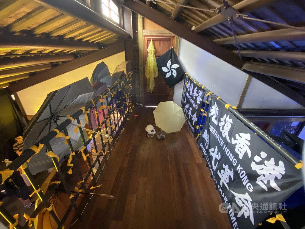 邊城青年籌劃主辦的「穿石 Surmount/香港騷動年代—抗志」展覽20日開幕,使用雨傘、防毒面具等道具,模擬去年香港「反送中」運動的街頭抗爭場景。中央社記者賴言曦攝 109年6月20日