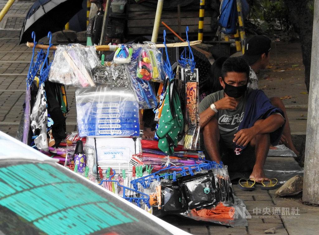 對菲律賓底層民眾而言,醫療級口罩價格難以負擔,他們多半選擇可重複使用的布口罩。圖為黎薩公園(Rizal Park)附近一名戴著布口罩的路邊小販,攝於15日。中央社記者陳妍君馬尼拉攝 109年6月20日