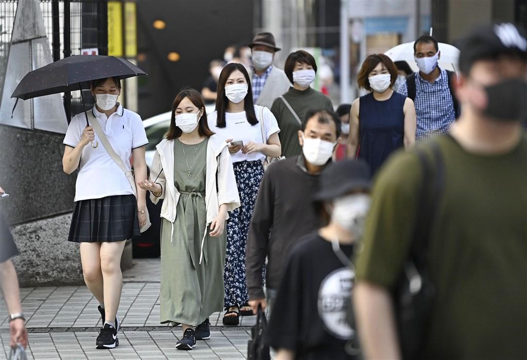 共同社報導,日本26日新增破百起武漢肺炎感染病例,為5月9日以來首見。圖為新宿車站前民眾戴口罩防疫。(共同社提供)