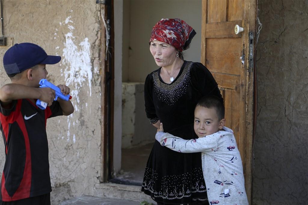哈薩克裔的歐米爾札克(中)家境極貧,她在中國出生,當菜販的丈夫正被拘留。她生下第3個孩子後,政府就命令她裝上子宮內避孕器,數年後4名著迷彩服的警官找上門,要她在3天內繳交2685美元罰款,因為她超生了一個孩子。(美聯社)