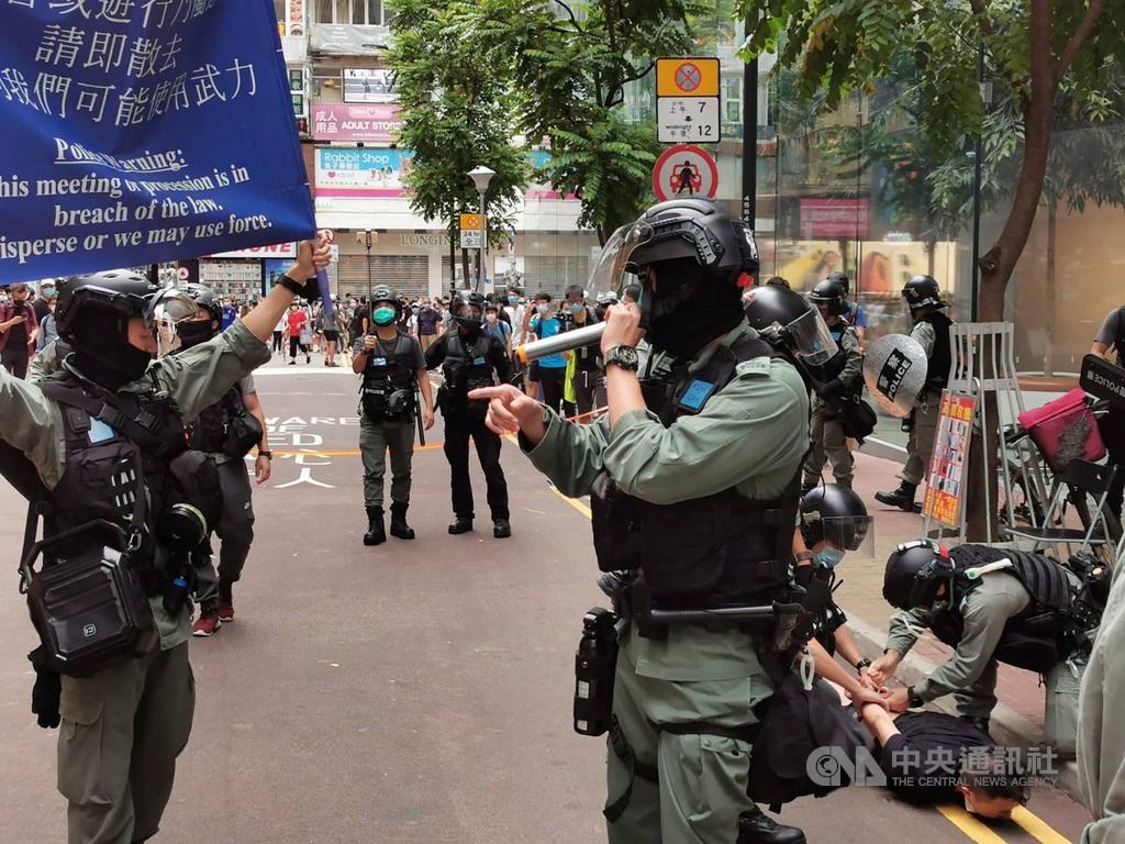 「港區國安法」6月30日深夜生效後,不少港人7月1日在銅鑼灣崇光百貨一帶遊行抗議。圖為下午2時許,警方驅趕附近聚集的人士,並逮捕一名示威者。中央社記者張謙香港攝 109年7月1日