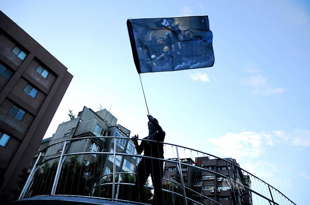 流亡來台的「反送中」示威者阿曦認為,若自己來台後不再為抗爭付出心力,就會成為逃兵。圖為阿曦揮舞著自製的「反送中」旗幟。中央社記者沈朋達攝 109年7月1日