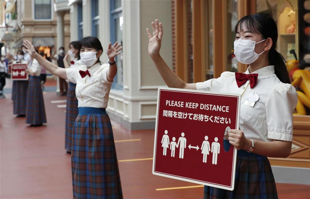 日本內閣官房長官菅義偉1日說,未來確診病例急速增加的話,最糟的情況有可能再度公布「緊急事態宣言」。圖為東京迪士尼工作人員宣導保持社交距離。(共同社提供)
