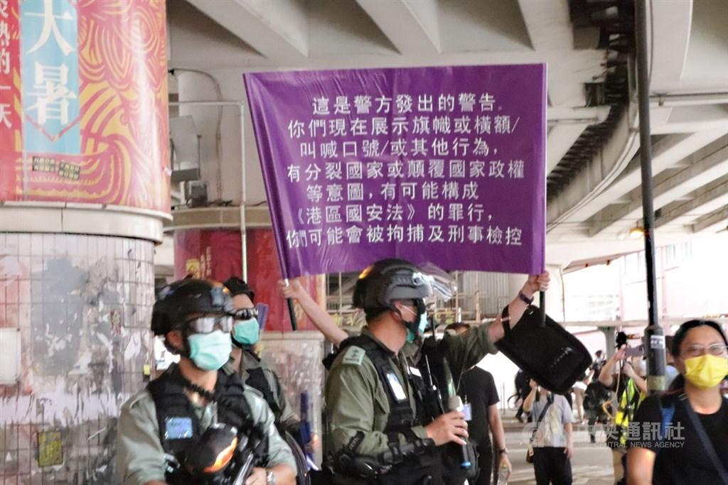 「港區國安法」生效後,英國宣布提供持國民海外護照港人更多居留權,澳洲也考慮提供港人安全庇護。圖為港警1日面對自行上街「七一」遊行的群眾,首度舉出了象徵執行「港區國安法」的紫色旗幟。中央社記者張謙香港攝 109年7月1日