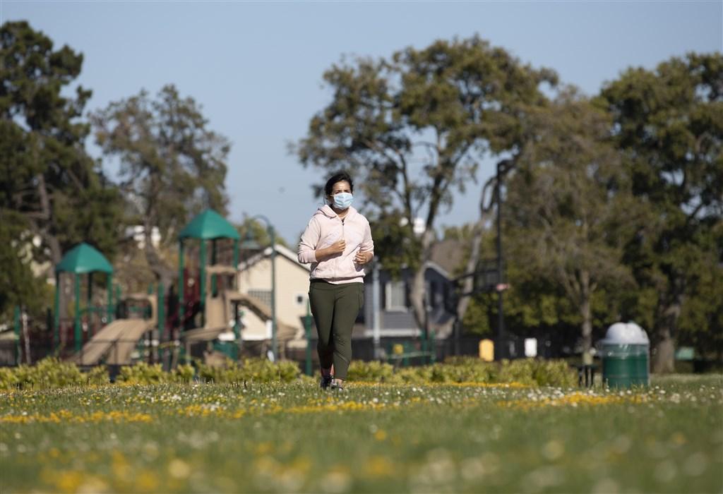 美國1日單日新增超過5萬2000起武漢肺炎確診病例,創單日新高紀錄。圖為6月30日美國加州民眾戴口罩在戶外跑步。(中新社提供)