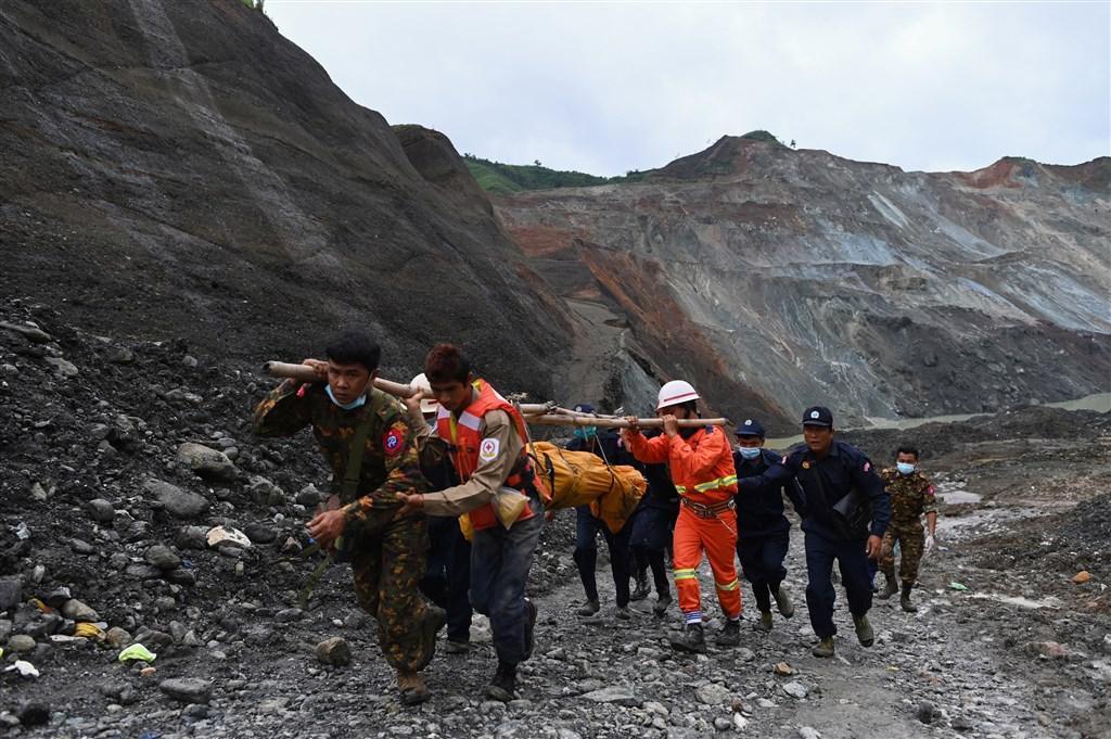 緬甸北部一處露天玉石礦場不堪連日豪雨坍方,罹難人數增至171人,為緬甸史上最嚴重礦災之一。圖為4日救災人員運出罹難者遺體。(法新社提供)