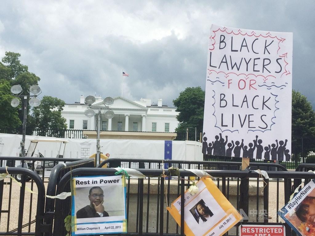 抗議民眾在圍欄掛上喪命非裔民眾照片及訴求,與美國最高權力機構白宮隔著圍欄相望。中央社記者江今葉華盛頓攝 109年6月19日