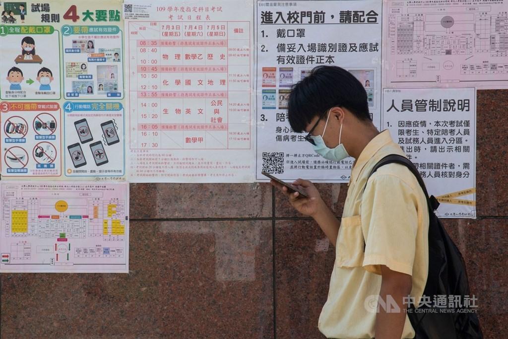 大學指考5日進行最後一天考試,配合防疫需求,考生必須戴著口罩入場。圖為新北考場門口等待進場的學生。中央社記者林俊耀攝 109年7月5日