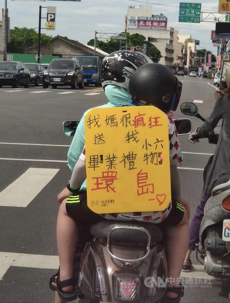 文史工作者蔣敏全在社群網站發文表示,他開車行經彰化溪湖鎮停等紅綠燈時,看到有一輛摩托車,媽媽載著孩子,孩子身上背著黃色字牌,寫著:「我媽很瘋狂送我小六畢業禮物(環島)」。(翻攝照片)中央社記者吳哲豪傳真 109年7月8日