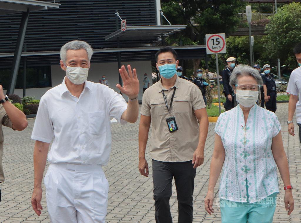 新加坡10日舉行國會大選,總理李顯龍夫婦赴雅德小學投票站投下神聖一票。圖為李顯龍(左)及夫人何晶(右)步出投票站向媒體揮手致意。中央社記者黃自強新加坡攝 109年7月10日
