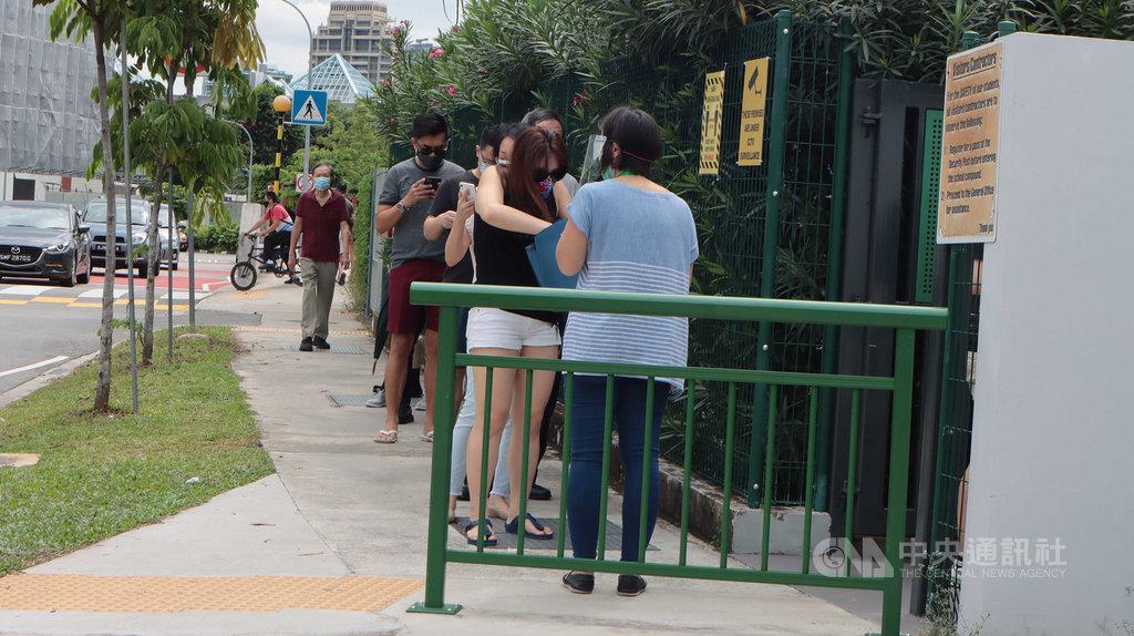 新加坡10日舉行國會大選,選舉局公告指出,投票時間將延長到晚間10時。圖為雅德小學投票站選民排隊投票。中央社記者黃自強新加坡攝 109年7月10日