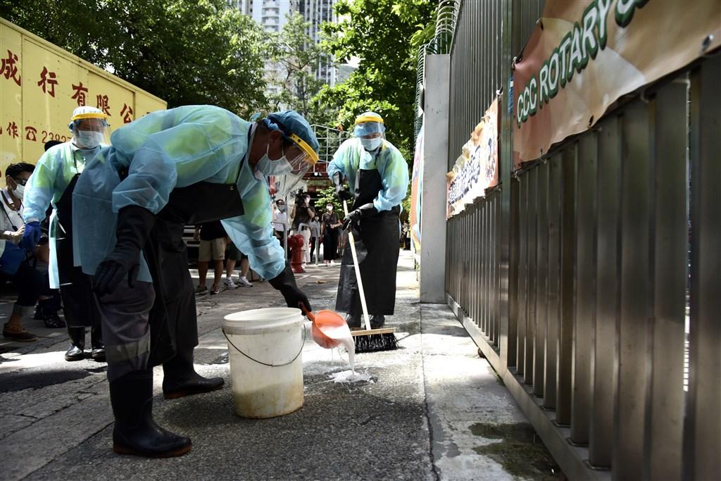 香港新冠肺炎病例增加,當局決定本地中小學和幼兒園13日起提前放暑假。圖為清潔人員在中華基督教會扶輪中學附近消毒。(中新社提供)