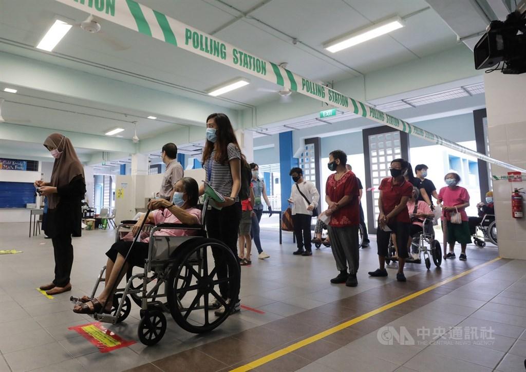 新加坡10日在疫情下舉行國會大選,選民保持社交安全距離,依序排隊進入德能中學投票站投票。中央社記者黃自強新加坡攝 109年7月10日