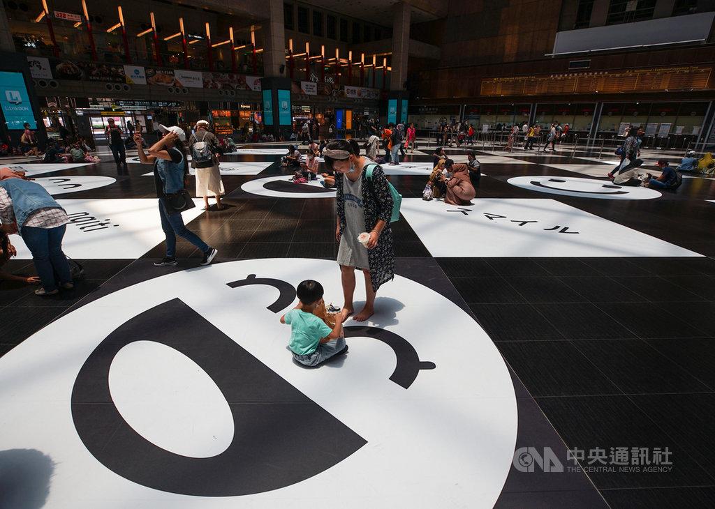 台鐵廣納各方意見,在台北車站大廳增加微笑地貼及寫著「微笑」的10種語文,希望展現友善與包容。不少民眾12日上午在北車大廳席地而坐,保持社交距離。中央社記者裴禛攝 109年7月12日