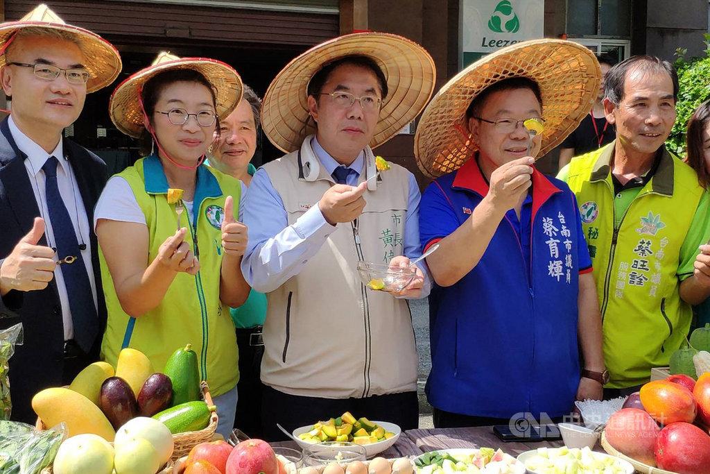 台南市長黃偉哲(中)12日在新營區協助農民叫賣,支持採友善耕作方式的多種農產品。中央社記者楊思瑞攝 109年7月12日