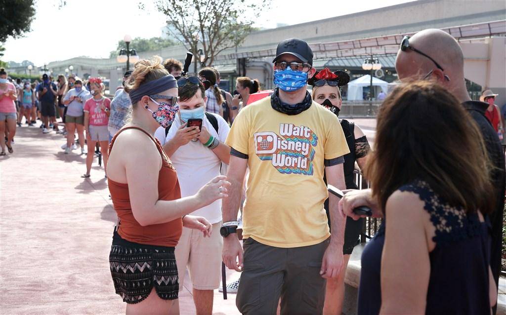 位於美國佛羅里達州的「迪士尼世界」11日重新開放,遊客排隊等候進入主題樂園「神奇王國」。(法新社提供)