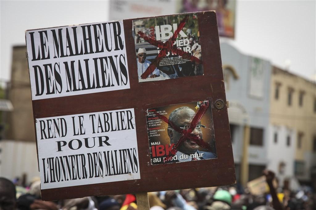西非國家馬利近來動盪不安,多名反對派領袖遭捕,而腹背受敵的總統凱塔11日宣布解散憲法法庭,試圖平息紛爭。圖為示威民眾高舉看板要求總統辭職下台。(美聯社)
