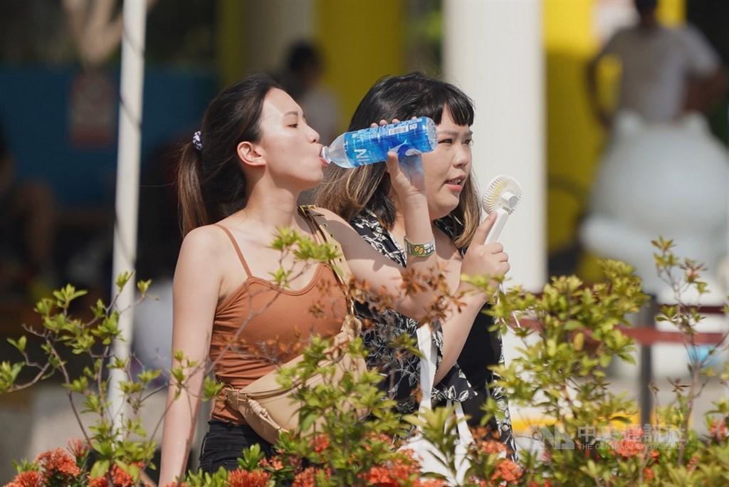 根據中央氣象局觀測,台北測站13日中午11時59分氣溫達攝氏38.9度,創下歷年7月最高溫紀錄,北市民眾在戶外喝飲料補充水分,也有人以隨身電扇消暑。中央社記者徐肇昌攝 109年7月13日