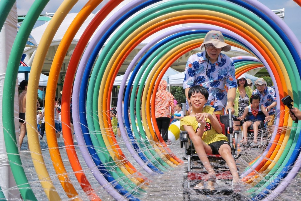 台北市第一座共融式親水遊樂場13日在兒童新樂園開幕,市長柯文哲(中後)親自推著坐輪椅的身心障礙小朋友穿越設施「套圈圈」,一同戲水消暑。中央社實習記者劉至柔攝 109年7月13日