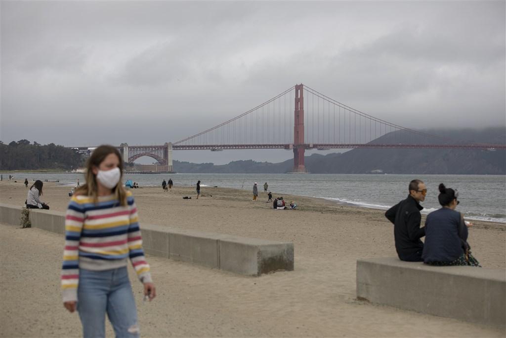 武漢肺炎已奪走全球逾56萬5000條人命,並有將近1300萬人確診。圖為3日舊金山海灘遊客戴口罩防疫。(中新社提供)