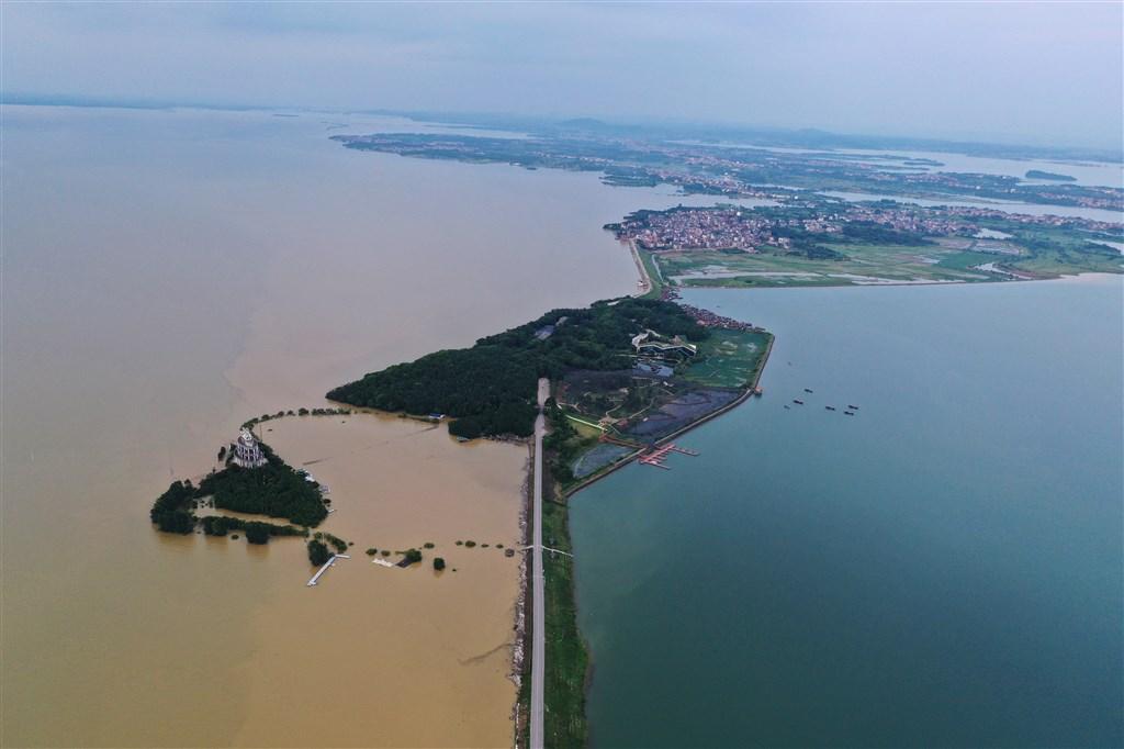 12日鄱陽湖水位超越1998年洪水,突破有水文紀錄以來的歷史高峰。圖為一側是清澈的鄱陽湖內湖珠湖,另一側是因暴雨變渾濁的鄱陽湖外湖。(中新社提供)
