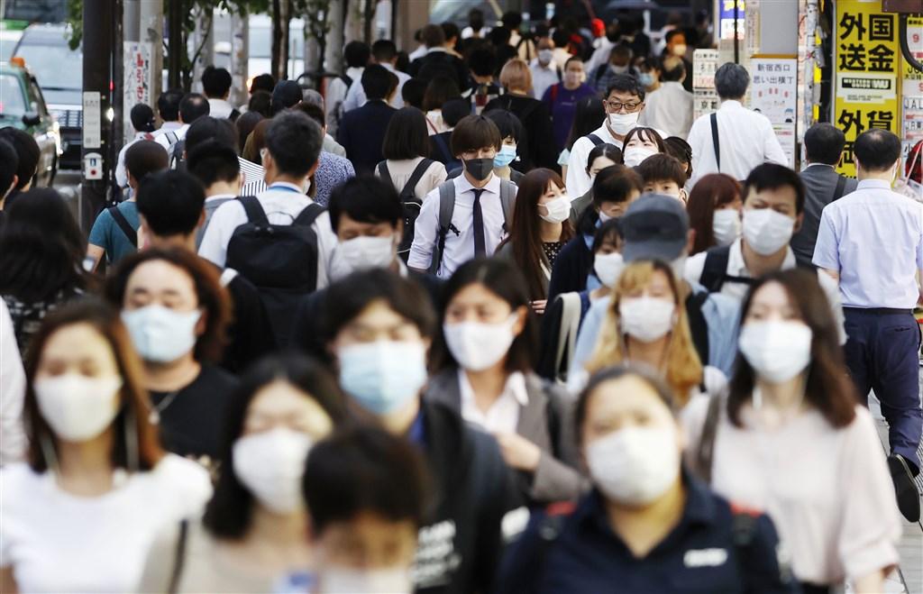 日本東京新宿區一座劇場發生武漢肺炎群聚感染,已知男星山本裕典及演員、工作人員、觀眾等59人確診。圖為15日新宿街頭人潮大多戴口罩防疫。(共同社提供)