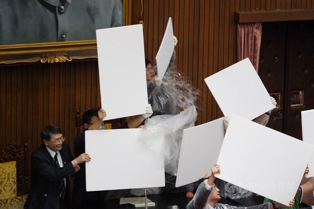 立法院會17日進行監察院人事同意權案投票,中午開票前,國民黨立委拿出預藏的水球,往主席台及票匭處猛丟,企圖阻止開票進行;民進黨立委則穿上雨衣,以保麗龍板保護立法院長游錫堃。中央社記者徐肇昌攝 109年7月17日