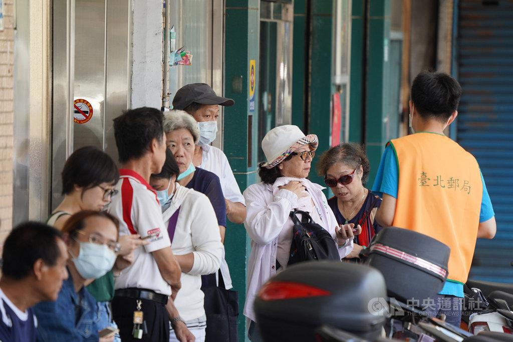 中華郵政發放振興三倍券,18日迎來首個假日,全台1269家郵局全日加班營業,不少民眾一早就到郵局,在工作人員引導下排隊購買三倍券。中央社記者徐肇昌攝 109年7月18日