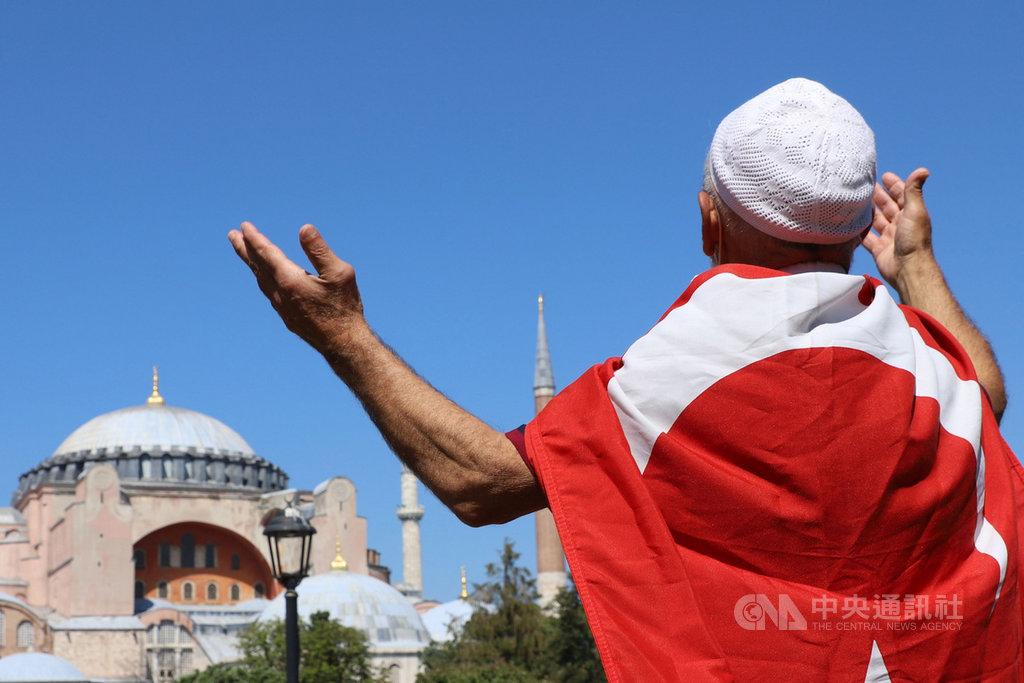 土耳其將擁有近1500年歷史的世界遺產聖索菲亞改成清真寺,24日將開放穆斯林進行86年來首場聚禮。一名穆斯林22日身披土耳其國旗,在建築前方祈禱。中央社記者何宏儒伊斯坦堡攝 109年7月23日