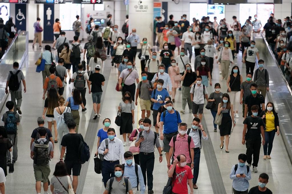 香港23日新增118例武漢肺炎確診病例,創下單日確診個案新高。圖為22日香港地鐵通道裡,民眾戴口罩防疫。(中新社)