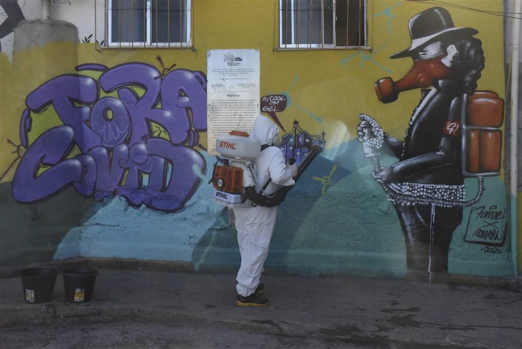 拉丁美洲武漢肺炎確診病例數首度超越美國和加拿大的合計確診數,成為全球最嚴重疫情災區。圖為25日巴西防疫人員在里約熱內盧南部的貧民窟消毒。(安納杜魯新聞社)