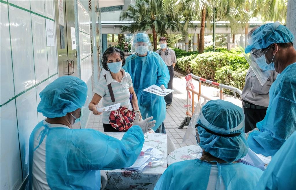 武漢肺炎持續在香港社區擴散,29日新增118例,累計確診個案達3002例。圖為民眾排隊做病毒檢測。(中新社)