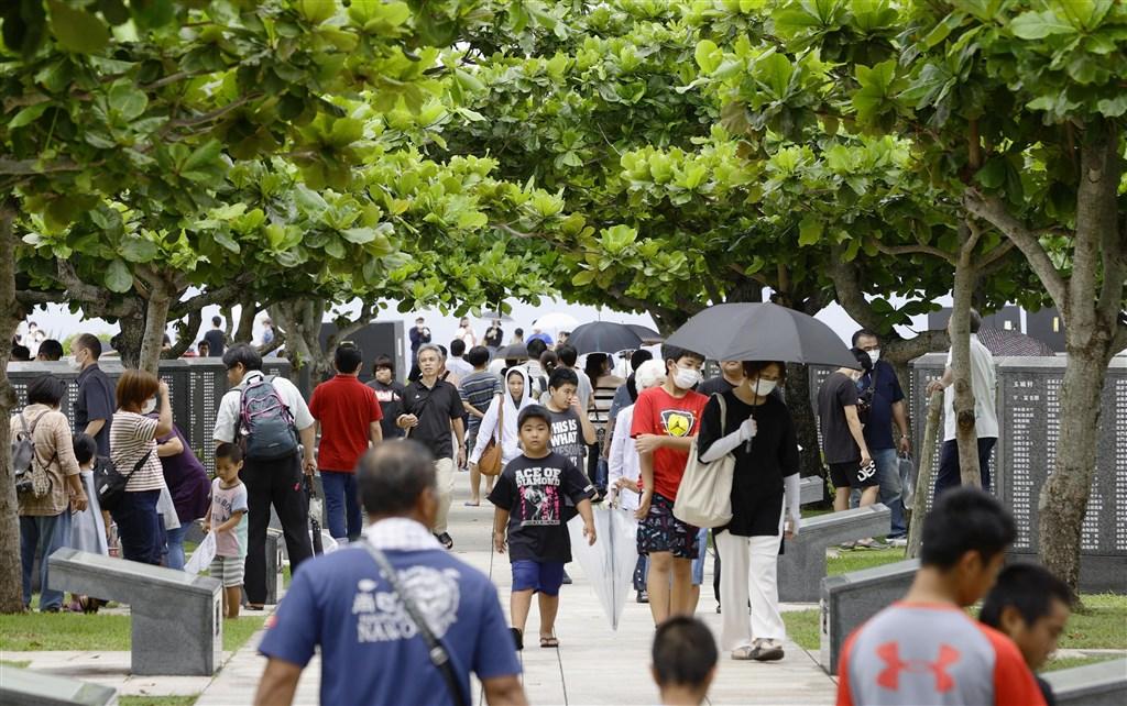 日本沖繩當地媒體31日報導,沖繩將自行宣布進入緊急狀態,並將縣內警示等級從第2階段流行警戒期提升至第3階段感染流行期。圖為沖繩部分民眾23日戴口罩前往當地公園。(共同社)