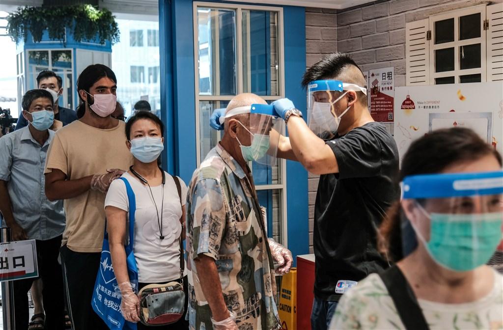 香港武漢肺炎疫情轉趨嚴峻,北京當局31日宣布,北京中央決定應香港方面要求派遣檢測人員赴港協助展開大規模核酸檢測篩查。圖為29日香港慈雲山市場人員為入場市民測量體溫。(中新社)