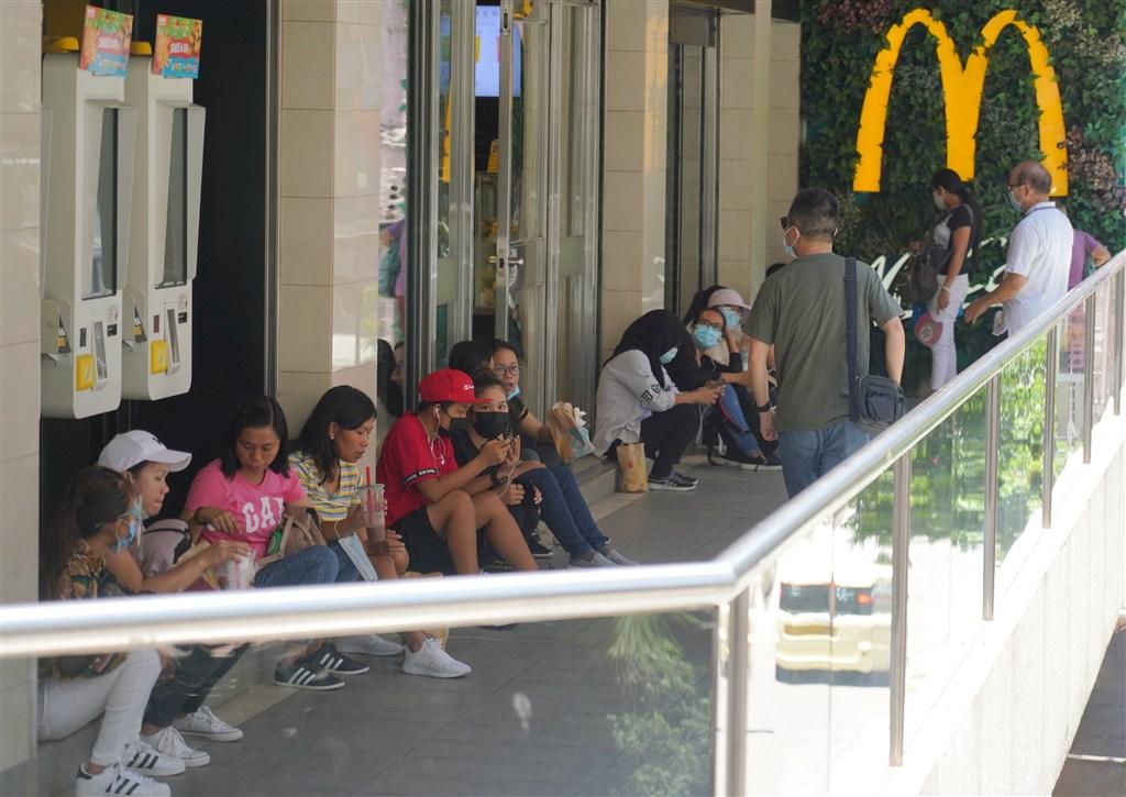香港為防疫情擴散,29日起禁止餐廳內用,但惹來民怨後決定放棄措施。圖為30日香港民眾因內容禁令在速食店外席地而坐用餐。(中新社)