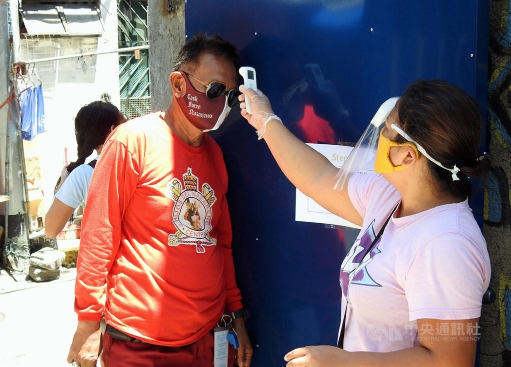 菲律賓武漢肺炎病例持續攀升,馬尼拉當局將要求大馬尼拉地區和呂宋島南部甲拉巴松區(Calabarzon)民眾出門須戴防護面罩。圖為菲國社福團體1日為領取物資的民眾量體溫。中央社記者陳妍君馬尼拉攝 109年7月31日