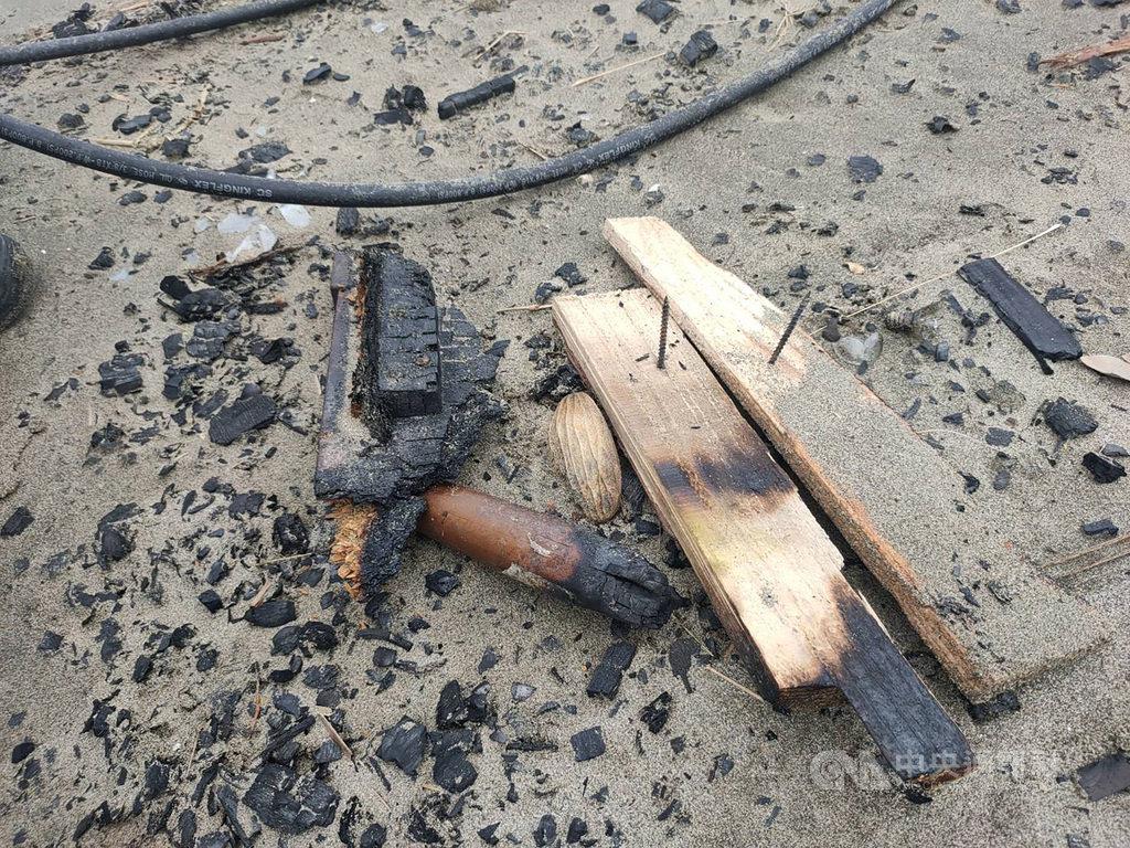 苗栗縣後龍鎮水尾地區沙岸疑有歌手前往拍攝MV,為劇情需求在沙灘上燃燒布景,卻遺留木板、鐵釘等廢棄物,環保局4日表示,將嘗試找出行為人負責清除並開罰。(民眾提供)中央社記者管瑞平傳真 109年8月4日