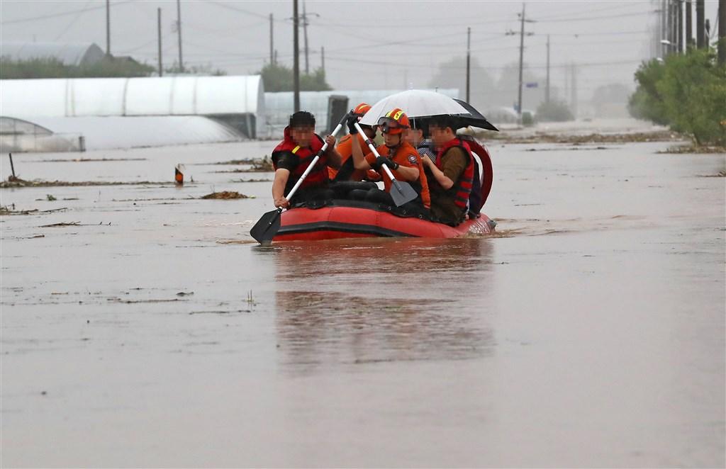 連日豪雨引發韓國洪災,根據當局統計,至今已造成至少13人喪生,超過1000名受災民眾流離失所。圖為3日天安市村民搭乘橡皮筏脫困。(韓聯社)