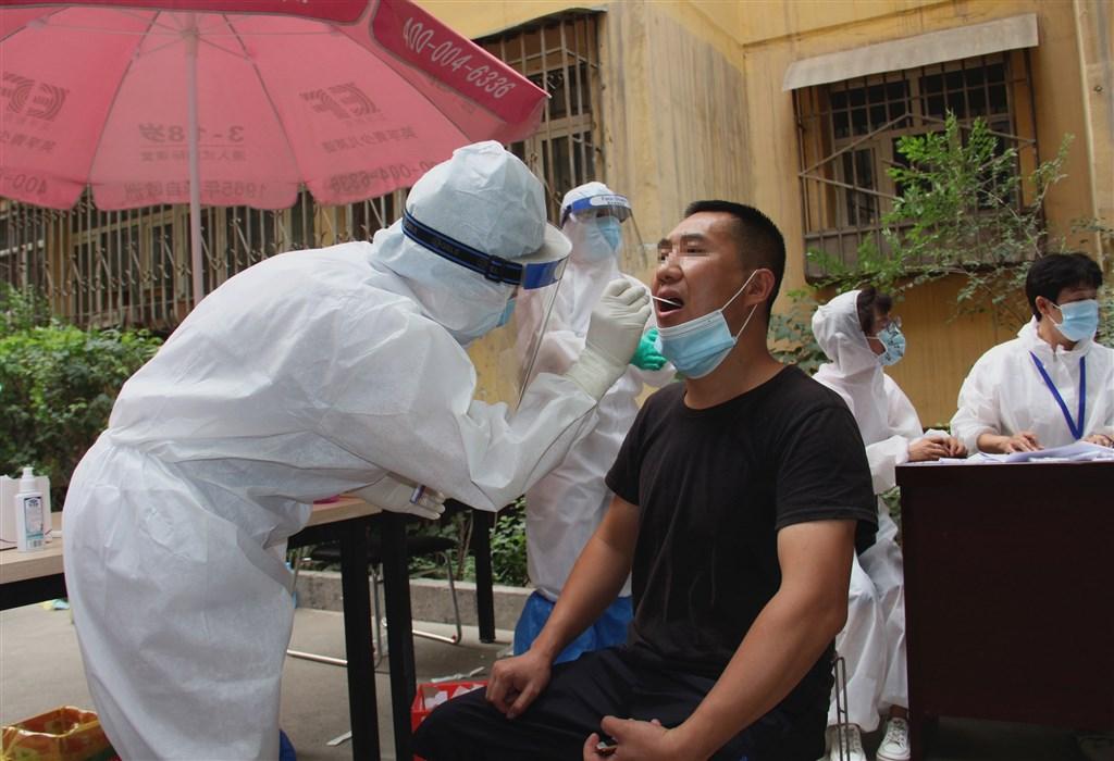 中國4日新增27例武漢肺炎病例,其中有22例本土病例,全都集中在新疆的烏魯木齊市。圖為烏魯木齊防疫人員為民眾進行核酸檢測。(中新社)