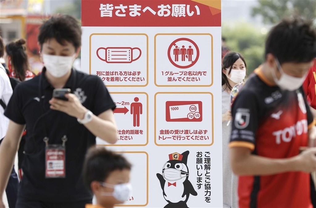日本境內武漢肺炎疫情蔓延,繼沖繩縣自行宣布「緊急事態宣言」後,愛知縣5日也跟進宣布,期間為6日至24日,呼籲民眾避免不必要的外出。圖為愛知縣民眾戴口罩至豐田體育場觀看足球賽。(共同社)