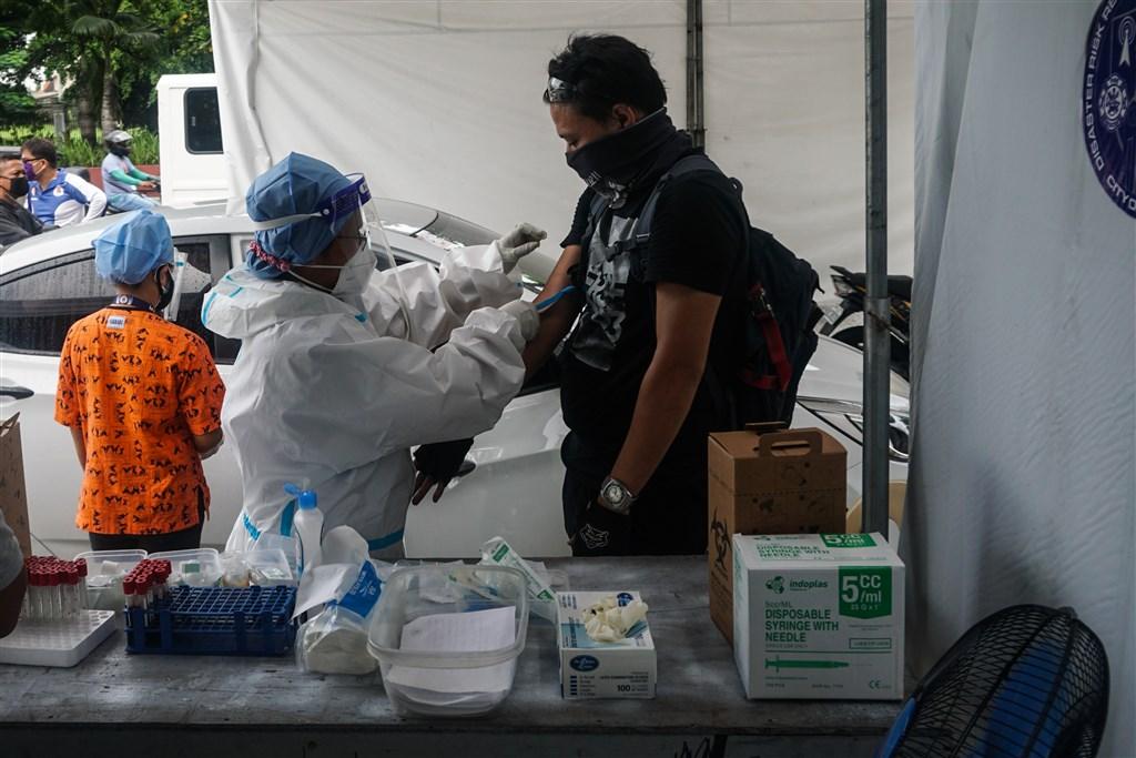 菲律賓4日創下東南亞單日最多人染疫的新紀錄,首都馬尼拉當天起恢復為期2週的部分封鎖措施。圖為菲律賓醫護人員為民眾抽血。(安納杜魯新聞社)