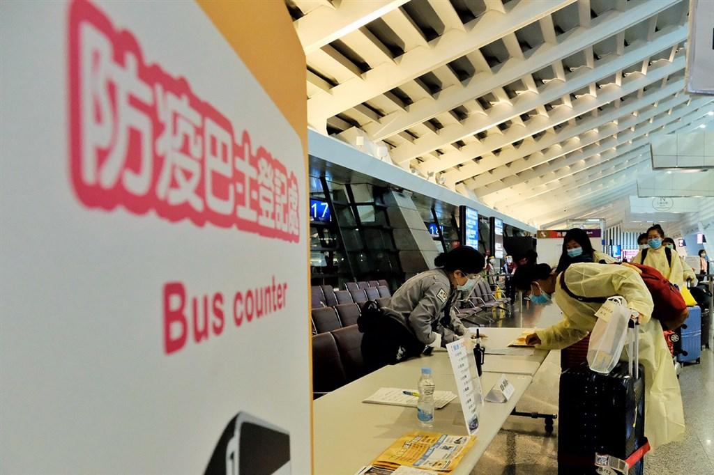 陽明大學研究顯示,台灣因政府效能高、人口老化程度高、病床數多,普篩對於降低死亡率的效果並不明顯。圖為桃園機場防疫車隊遊覽車載送返台旅客前往檢疫所集中隔離。(中央社檔案照片)