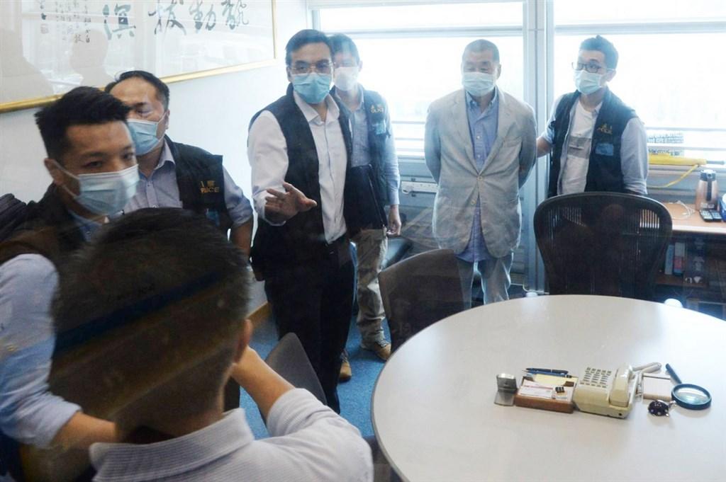 香港傳媒大亨黎智英(右2)被扣上手銬,押送到蘋果日報大樓內協助查證。(讀者提供)中央社記者張謙香港傳真 109年8月10日
