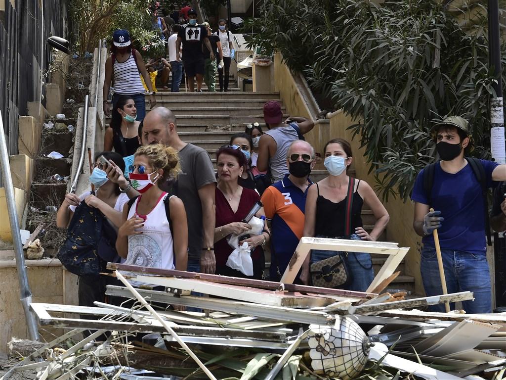 黎巴嫩首都貝魯特港口4日發生災難性大爆炸,醫療機構擠滿傷患之際,武漢肺炎新增病例又創新高。圖為貝魯特居民在斷垣殘壁中等待街道清理。(安納杜魯新聞社)