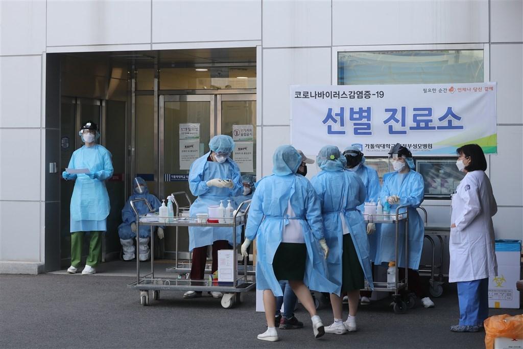 韓國中央防疫對策本部通報,韓國14日新增103例確診,其中85例為本土病例,為自3月底以來最多的社區感染病例。圖為韓國京畿道一間醫院醫護人員在院外設立篩檢站。(韓聯社)