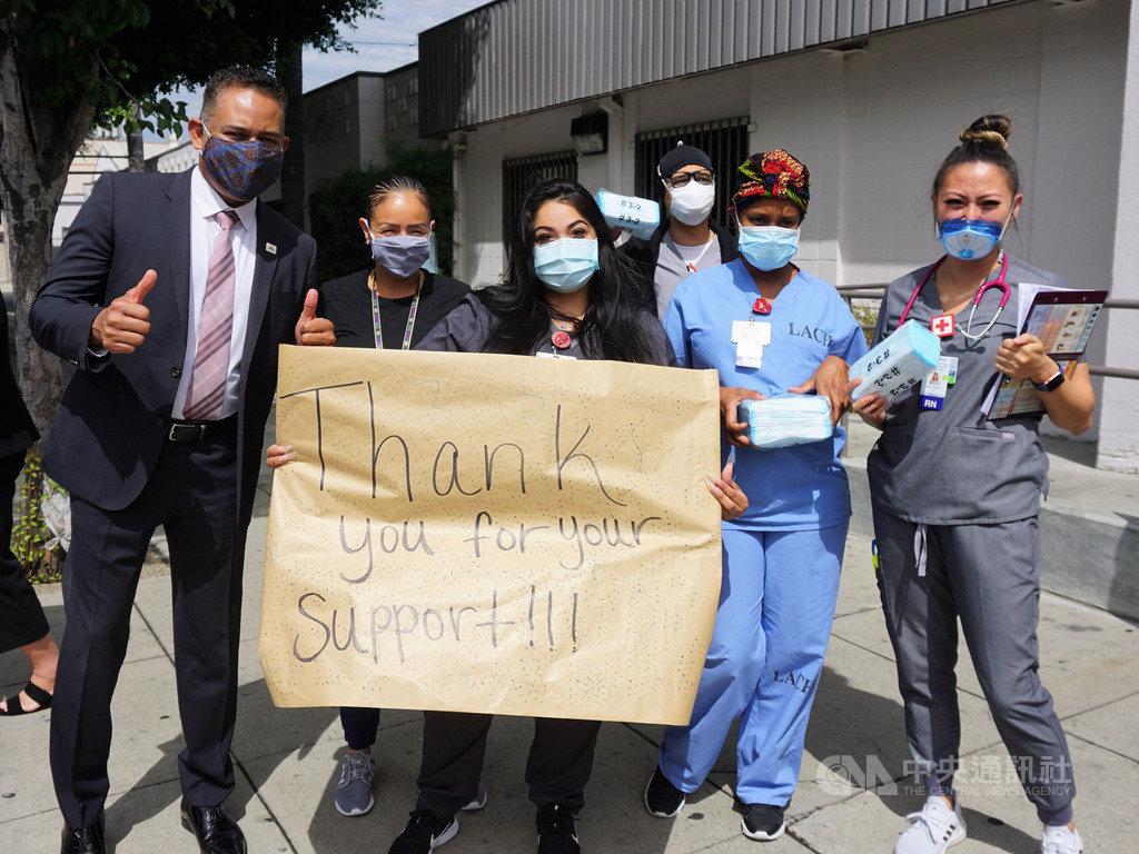 洛杉磯台美商會13日捐5萬片口罩給洛杉磯社區醫院(Los Angeles Community Hospital)。醫護人員出門相迎,拿手寫的海報致謝。中央社記者林宏翰洛杉磯攝 109年8月14日
